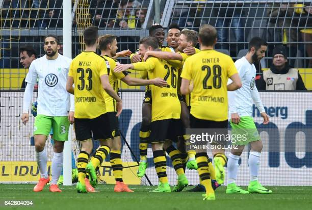 Dortmund's players celebrate during the German First division Bundesliga football match Borussia Dortmund vs VfL Wolfsburg in Dortmund on February 18...