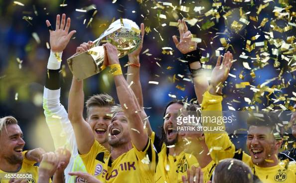 Dortmund's players celebrate with the trophy after winning the German Supercup football match Borussia Dortmund vs Bayern Munich in the German city...