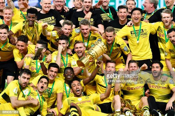 TOPSHOT Dortmund's players celebrate with the trophy after winning the German Cup final football match Eintracht Frankfurt v BVB Borussia Dortmund at...