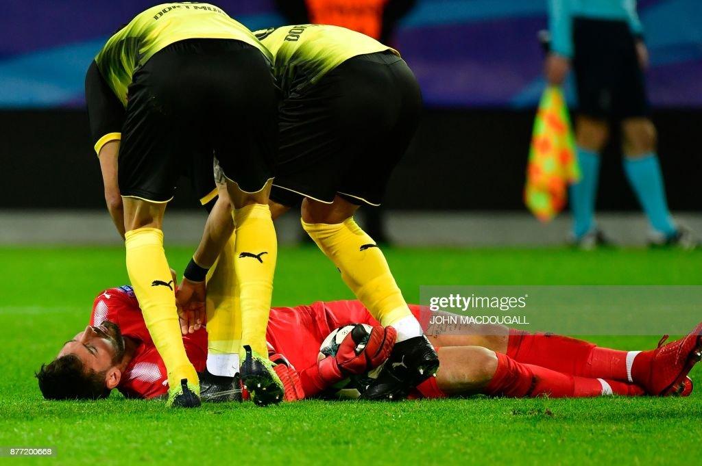 Dortmund's players chcek on their injured Swiss goalkeeper Roman Buerki during the UEFA Champions League Group H football match BVB Borussia Dortmund v Tottenham Hotspur at the BVB Stadion on November 21, 2017 in Dortmund, western Germany. / AFP PHOTO / John MACDOUGALL