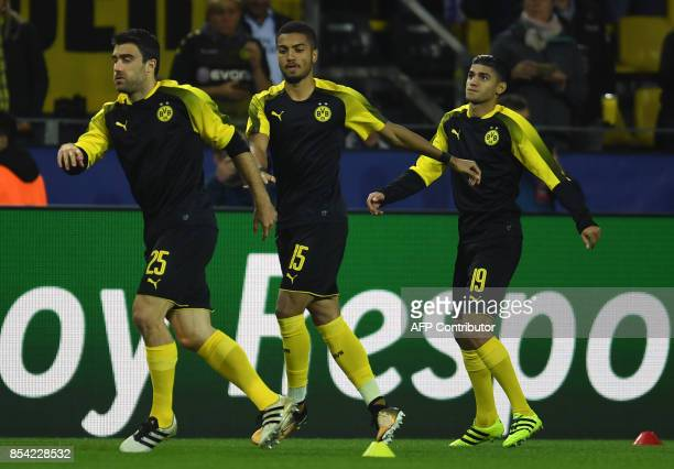 Dortmund's players Greek defender Sokratis German defender Jeremy Toljan and German midfielder Mahmoud Dahoud warm up prior to the UEFA Champions...