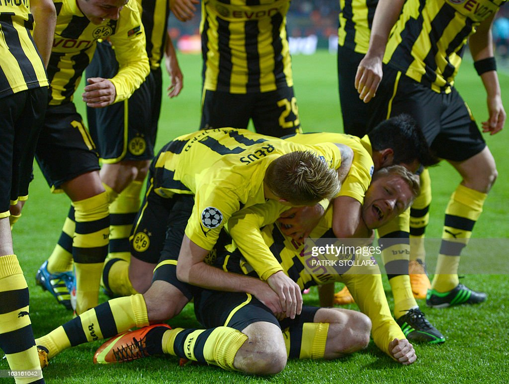 Dortmund's Polish midfielder Jakub Blaszczykowski (down, R) is congratulated by his teammates after scoring the 3-0 during the UEFA Champions League last 16, second leg match Borussia Dortmund vs Shakhtar Donetsk in Dortmund, western Germany, on March 5, 2013.