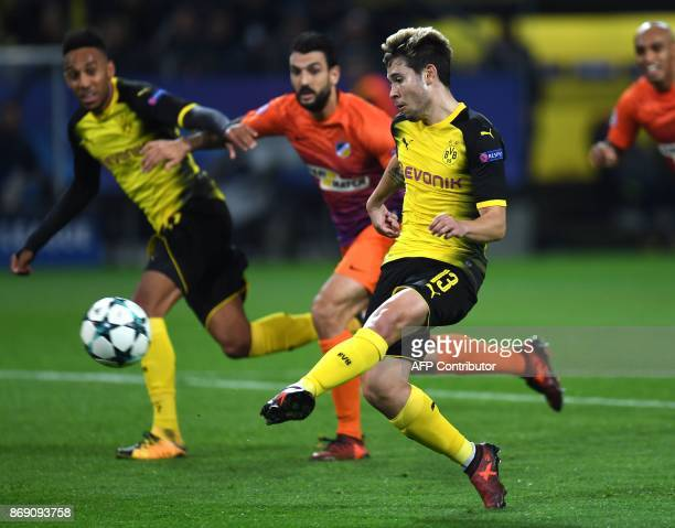 Dortmund's Portuguese defender Raphael Guerreiro scores the opening goal during the UEFA Champions League Group H football match BVB Borussia...