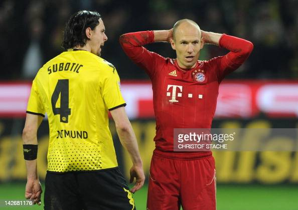 Dortmund's Serbian defender Neven Subotic and Bayern Munich's Dutch midfielder Arjen Robben react after the penalty kick during the German first...