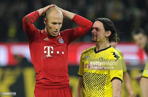Dortmund's Serbian defender Neven Subotic and Bayern Munich's Dutch midfielder Arjen Robben react after Robben missed the penalty kick during the...