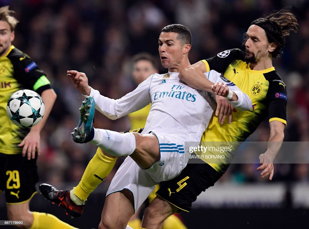 TOPSHOT - Dortmund's Serbian defender Neven Subotic (R) vies with Real Madrid's Portuguese forward Cristiano Ronaldo during the UEFA Champions League group H football match Real Madrid CF vs Borussia Dortmund at the Santiago Bernabeu stadium in Madrid on December 6, 2017. /