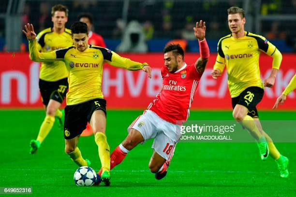 Dortmund's Spanish defender Marc Bartra and Benfica's Argentinian forward Eduardo Salvio vie for the ball during the UEFA Champions League Round of...