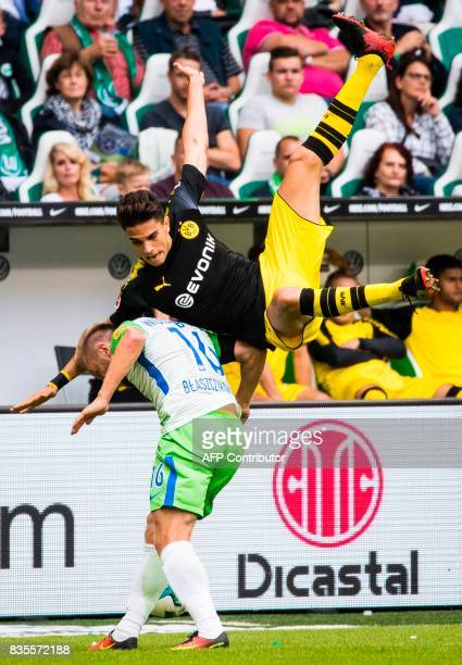 Dortmund´s Spanish defender Marc Bartra and Wolfsburg's Polish midfielder Jakub Blaszczykowski collide during the German first division Bundesliga...