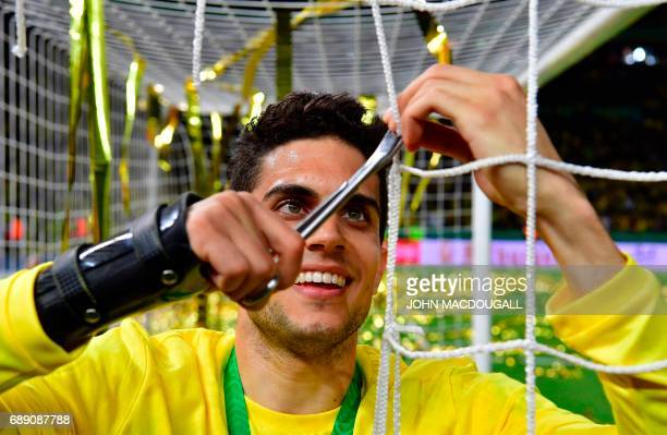 Dortmund's Spanish defender Marc Bartra cuts a piece of the net from the goal after the German Cup final football match Eintracht Frankfurt v BVB...