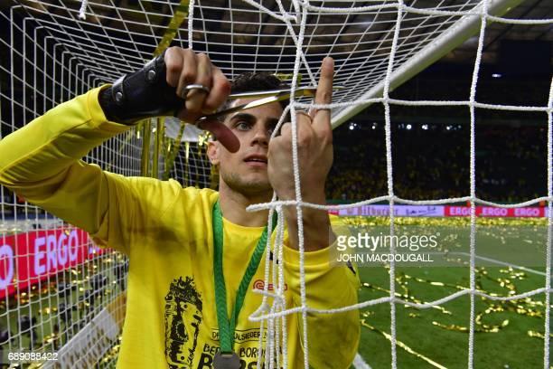 Dortmund's Spanish defender Marc Bartra cuts a piece of the net of the goal after the German Cup final football match Eintracht Frankfurt v BVB...