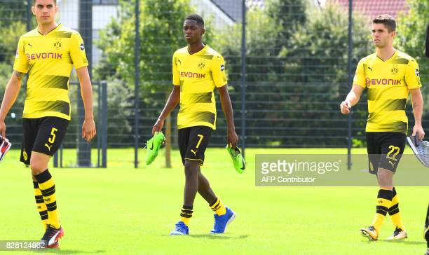 Dortmund's Spanish defender Marc Bartra Dortmund's French midfielder Ousmane Dembele and Dortmund's US midfielder Christian Pulisic walk over the...