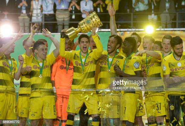 Dortmund's Spanish defender Marc Bartra lifts the trophy as Dortmund's players celebrate with the trophy after winning the German Cup final football...