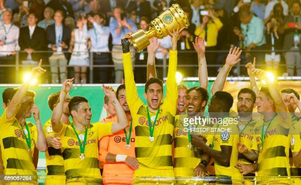 Dortmund's Spanish defender Marc Bartra lifts the trophy as Dortmund's players celebrate after winning the German Cup final football match Eintracht...