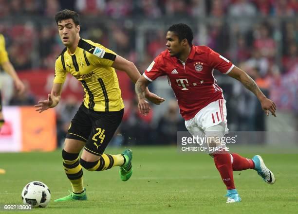 Dortmund's Spanish midfielder Mikel Merino and Bayern Munich's Brazilian midfielder Douglas Costa vie during the German first division Bundesliga...