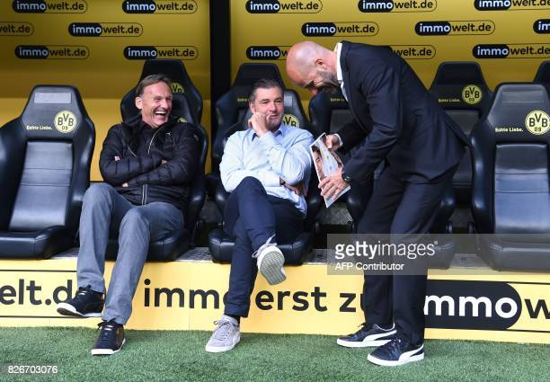 Dortmund's Sport director Michael Zorc CEO HansJoachim Watzke and Dortmund's Dutch head coach Peter Bosz chat prior to the German Supercup football...