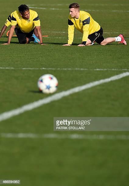 Dortmund's striker Marco Reus and Dortmund's Gabonese striker PierreEmerick Aubameyang warm up during a training session on the eve of the Round of...