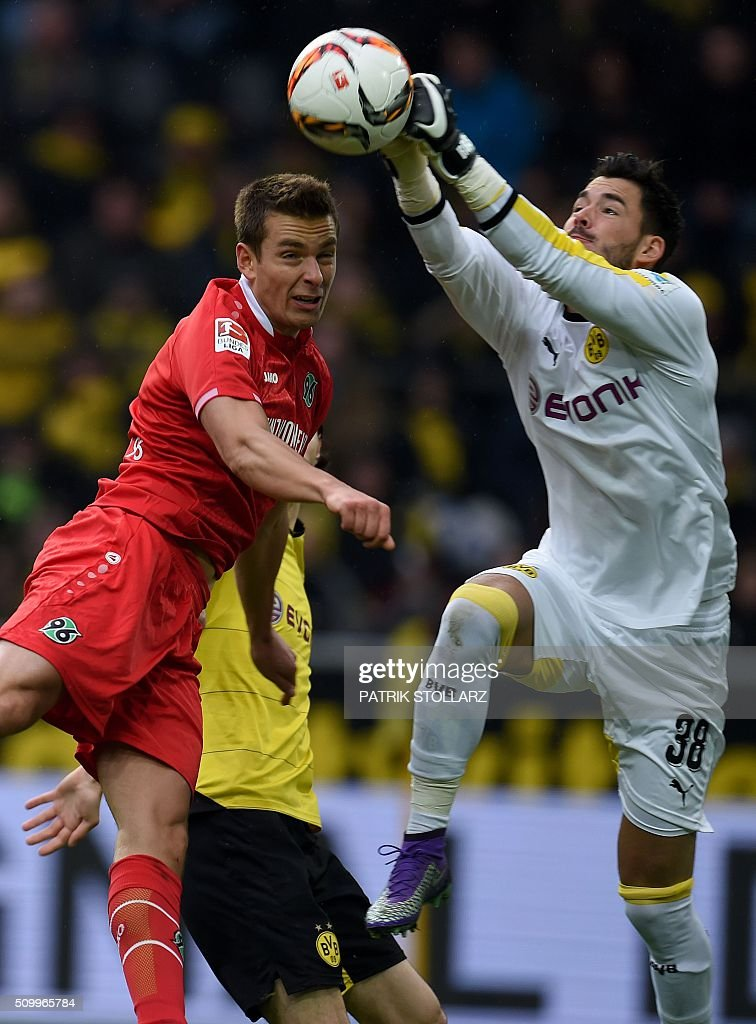 Dortmund's Swiss goalkeeper Roman Buerki and Hanover's Polish striker Artur Sobiech vie for the ball during the German first division Bundesliga football match of Borussia Dortmund vs Hannover 96 in Dortmund, western Germany, on February 13, 2016. / AFP / PATRIK STOLLARZ /