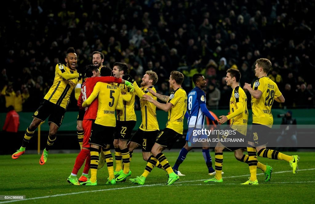 Dortmund's Swiss goalkeeper Roman Buerki celebrates with his teammates after the penalty shoot-out of the German Cup DFB Pokal round of 16 football match BVB Borussia Dortmund v Hertha Berlin in Dortmund, western Germany on February 8, 2017.