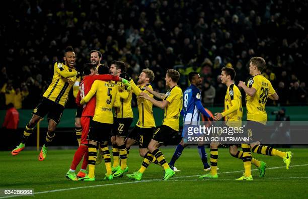 Dortmund's Swiss goalkeeper Roman Buerki celebrates with his teammates after the penalty shootout of the German Cup DFB Pokal round of 16 football...