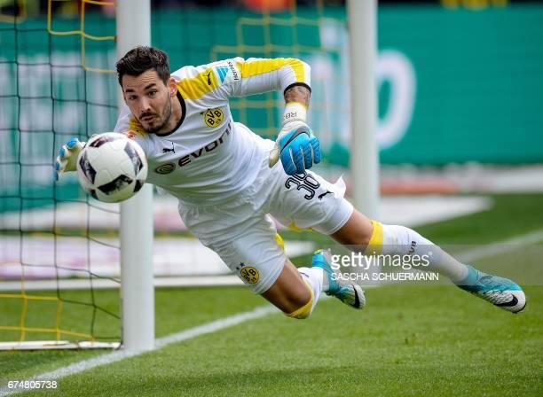 Dortmund's Swiss goalkeeper Roman Buerki reaches for the ball during the German first division Bundesliga football match between Borussia Dortmund...