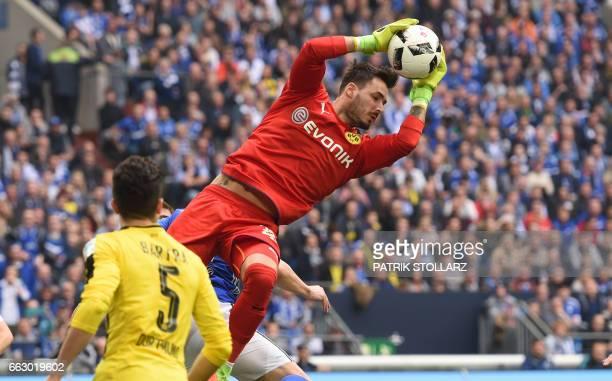Dortmund's Swiss goalkeeper Roman Buerki saves the ball during the German First division Bundesliga football match between FC Schalke 04 and Borussia...