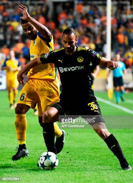 Dortmund's Turkish defender Omer Toprak is marked by APOEL Nicosia's Dutch forward Lorenzo Ebicilio during the UEFA Champions League football match...