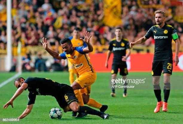 Dortmund's Turkish defender Omer Toprak is tackled by APOEL Nicosia's Dutch forward Lorenzo Ebicilio during the UEFA Champions League football match...