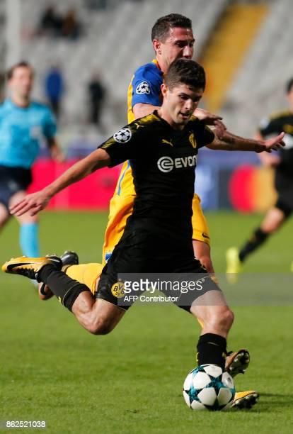 Dortmund's US midfielder Christian Pulisic kicks the ball as APOEL Nicosia's Spanish defender Roberto Lago defends during the UEFA Champions League...