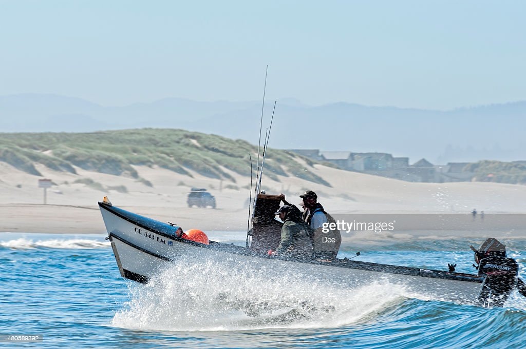 Dory Boat cuts through waves to land on beach : Stock Photo
