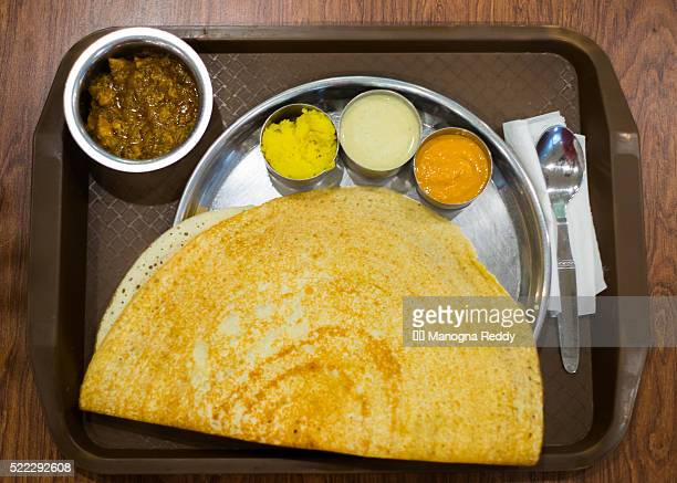 Dosa served in a plate along with chettinad chicken and sambar