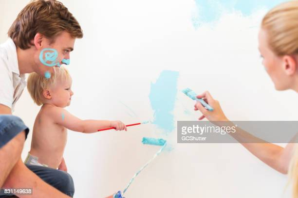 Doting parents patiently watching their child play and paint his new room wall