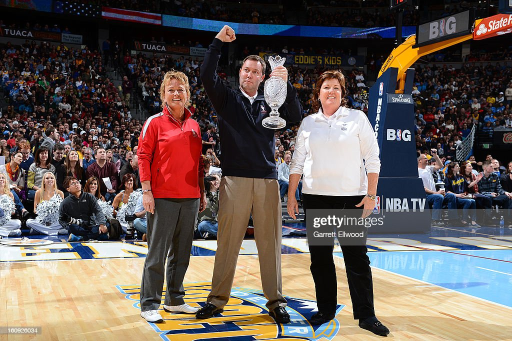 Dottie Pepper, LPGA Commissioner Mike Whan, and U.S. Team Captain Meg Mallon take a picture with the Solheim Cup at halftime during the game between the Denver Nuggets and Chicago Bulls on February 7, 2013 at the Pepsi Center in Denver, Colorado.
