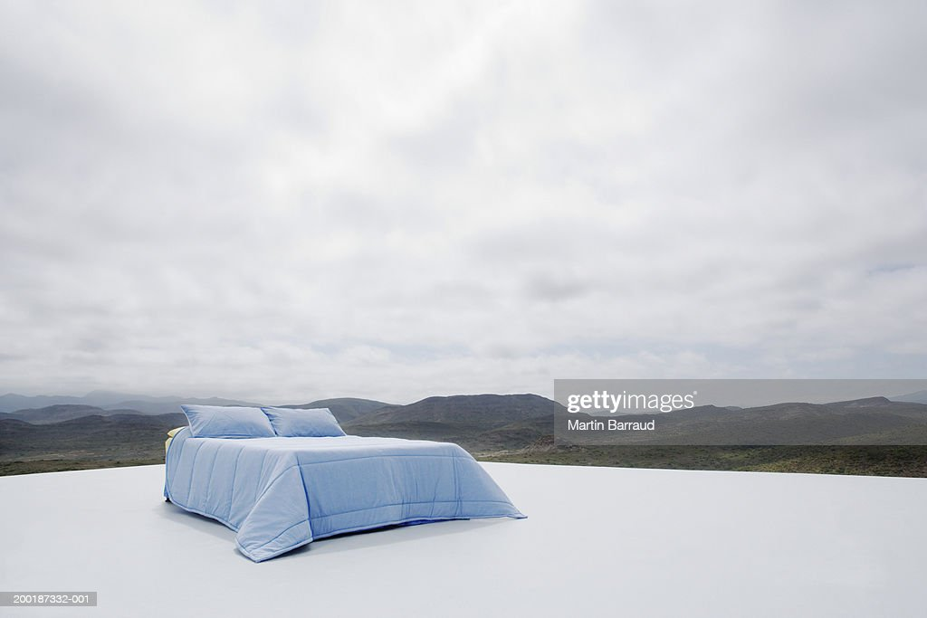 Double bed on platform overlooking rugged landscape