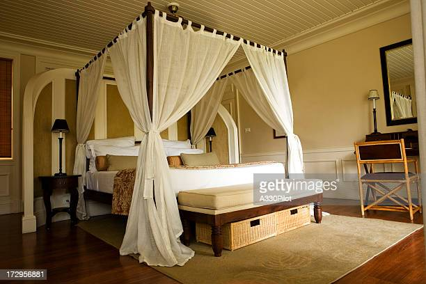 Double bed with white curtains