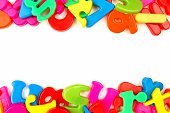 Double border of colorful toy magnetic letters and numbers over a white background