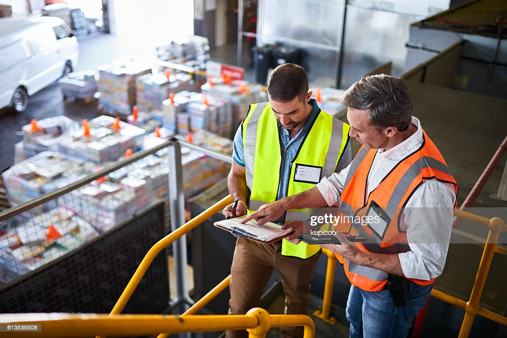 Double checking their shipping schedule : Foto de stock