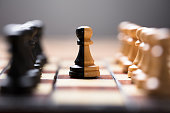 Closeup of double color pawn amidst other chess pieces on board game