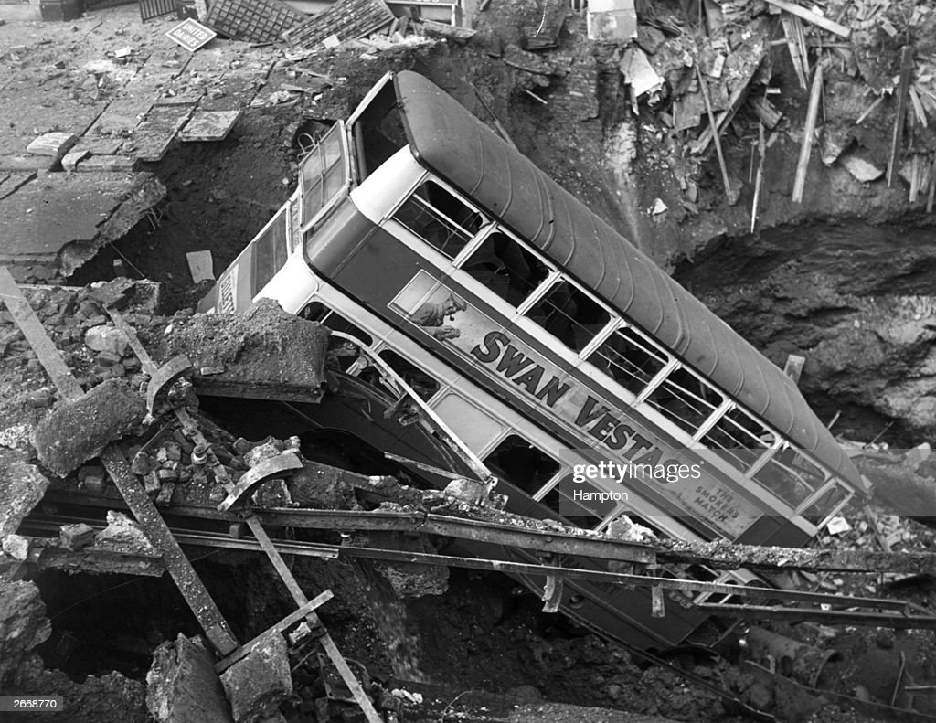 A double decker bus, advertising Swan Vesta matches, in a bomb crater in Balham, London, during the Blitz.