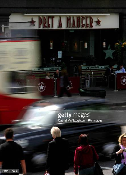 A double decker bus and a London taxi pass the Trafalgar Square branch of sandwich shop Pret A Manger in central London