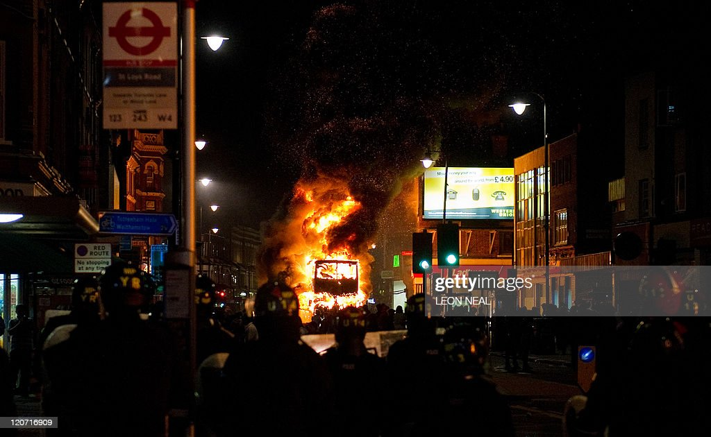 A double decker bus burns as riot police : News Photo