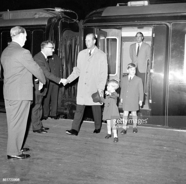 Double duty for Prince Philip The Duke of Edinburgh as he copes with his hat and the clutching hand of Prince Edward at Kings Cross Station London...