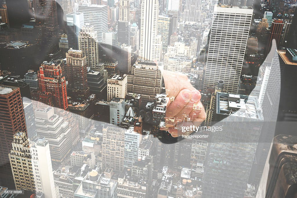 double exposure business handshake on the financial district