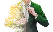 Double exposure businessman in green suit with big tree and sunlight, isolated on white background