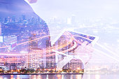 Double exposure businessman using tablet and cityscape night view, Business technology concept
