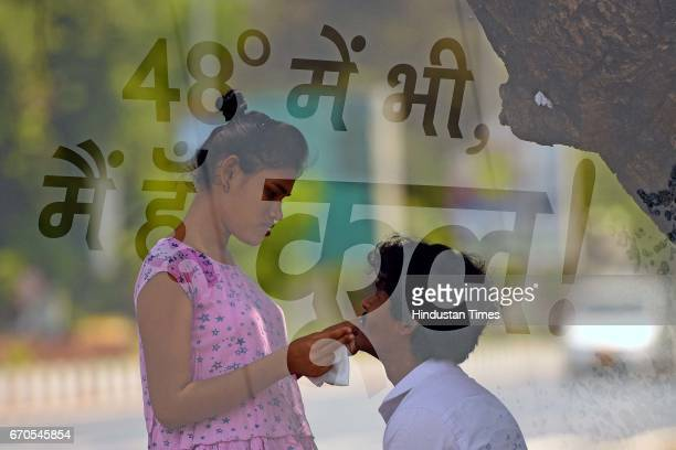Double exposure of a girl sweeping sweat of her partner during a hot sunny day at Marine Drive on April 19 2017 in Mumbai India Mumbai maintains its...