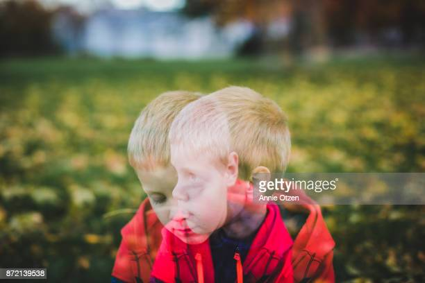 Double exposure of a sad little boy