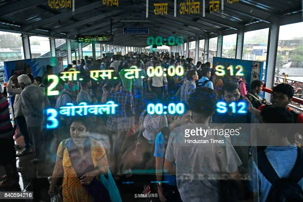A double exposure of a screen and people waiting for train as train services have been stopped at Ville Parle on August 29 2017 in Mumbai India...