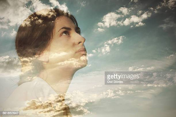 Double exposure of a young woman and cloudy sky