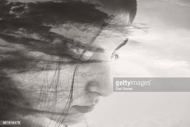 Double exposure of a young woman's face and clouds