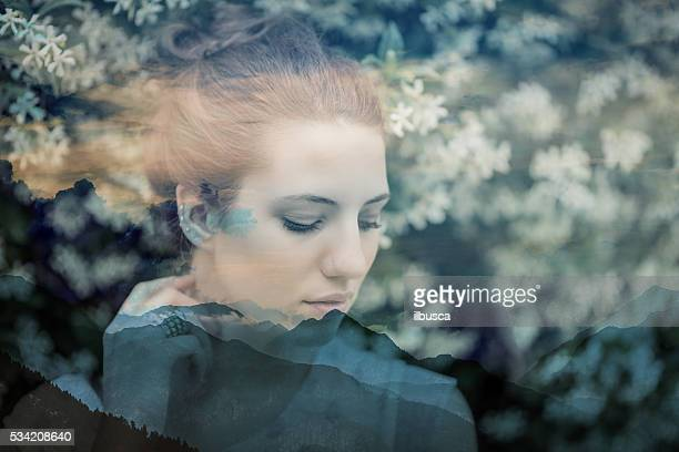 Double exposure of beautiful woman portrait in nature and mountains